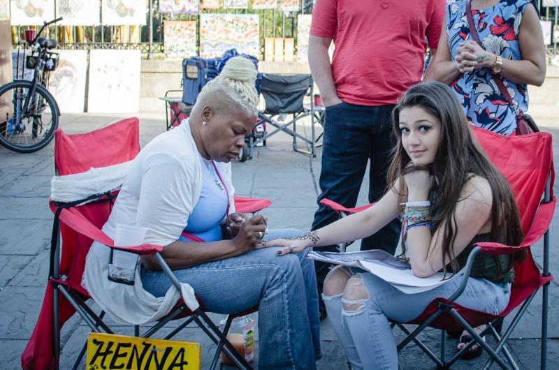 Touristin bekommt ein Henna-Tattoo von einer Straßenküstlerin am Jackson Square